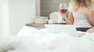 videoblocks-a-woman-smiles-beautifully-drinks-wine-and-communicates-on-the-internet-using-a-laptop-beautiful-young-woman-in-her-bright-bedroom-drinking-wine-and-talking-on-the-internet-u
